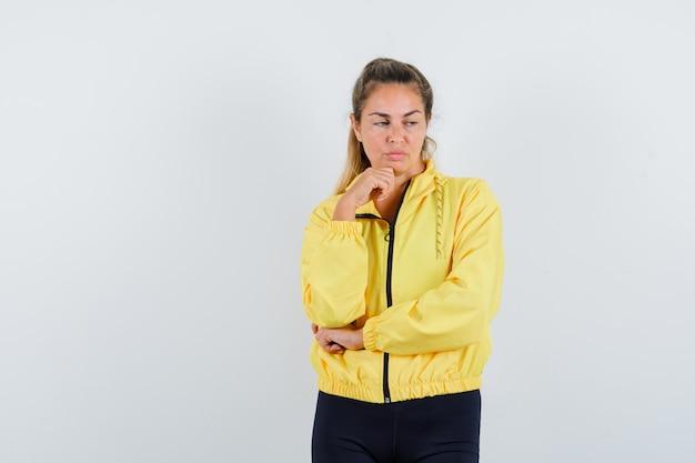 Блондинка в желтой куртке-бомбардировщике и черных штанах стоит в позе размышлений, опершись подбородком на руку и задумчиво смотрит