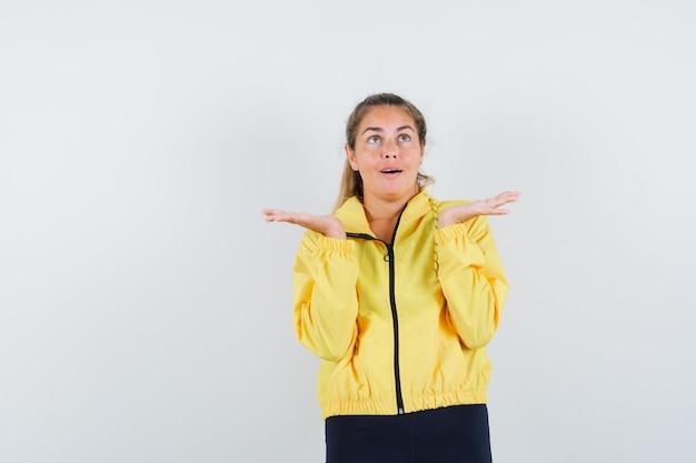 노란색 폭격기 재킷과 검은 색 바지에 금발의 여자가 뭔가를 들고 예쁜 것처럼 손을 뻗어