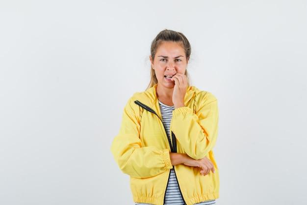 黄色のボンバージャケットとストライプのシャツを着た金髪の女性がポーズを考えて物思いにふけるように立っている間指を噛む