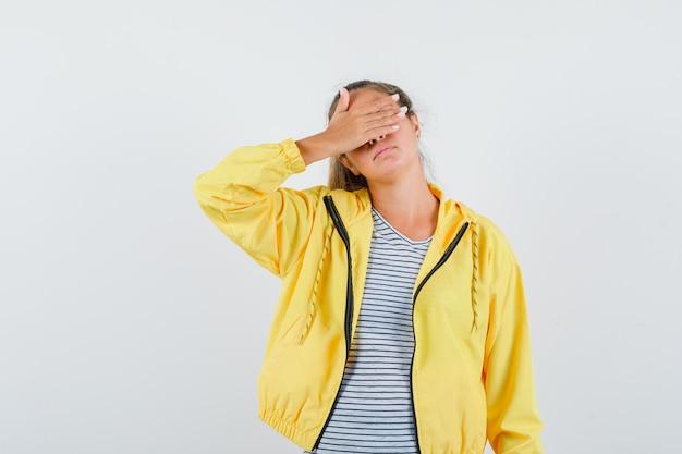 黄色のボンバージャケットとストライプのシャツを着た金髪の女性が口の手を覆い、真剣に見える