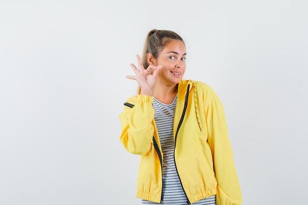 黄色のボンバージャケットとストライプのシャツを着た金髪の女性