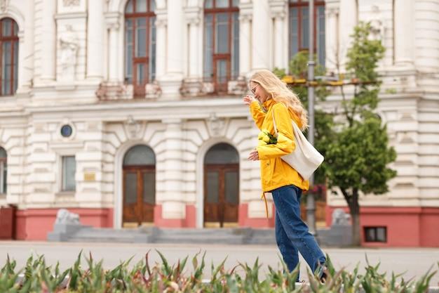 黄色いレインコートを着た金髪の女性が街を歩き回る