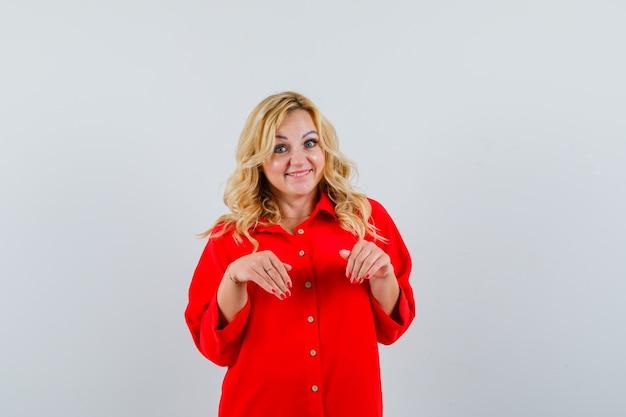 赤いブラウスに来て幸せそうに見える金髪の女性、正面図。