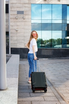 A blonde woman is happy with the suitcase goes summer in travel travelling by plane
