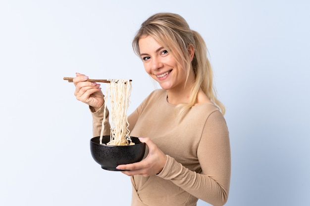 Blonde woman over isolated blue holding a bowl of noodles with chopsticks