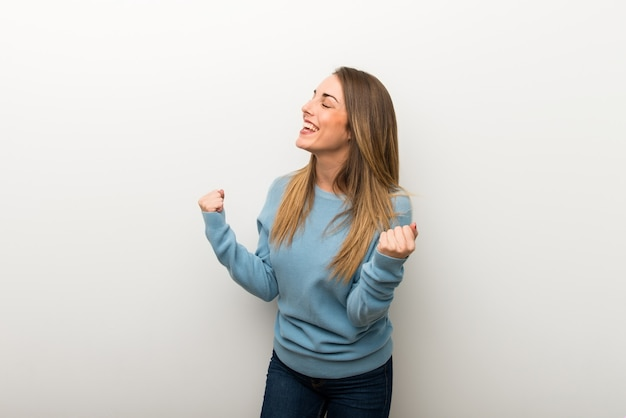 Blonde woman on isolated white background celebrating a victory