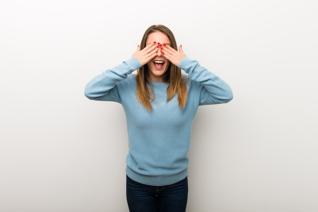 Blonde woman on isolated white background covering eyes by hands. surprised to see what is ahead