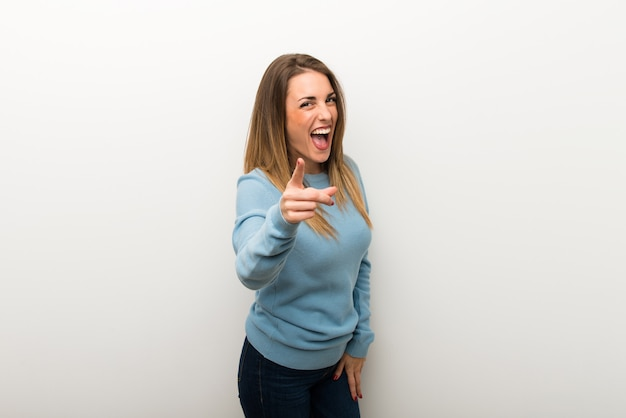 Blonde woman on isolated white background frustrated by a bad situation and pointing to the front