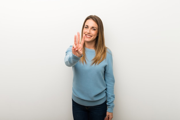 Blonde woman on isolated white background happy and counting three with fingers