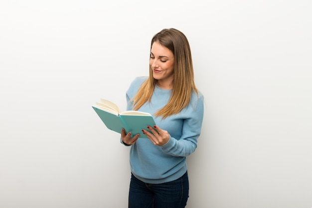 Blonde woman on isolated white background holding a book and enjoying reading