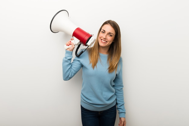 Blonde woman on isolated white background holding a megaphone