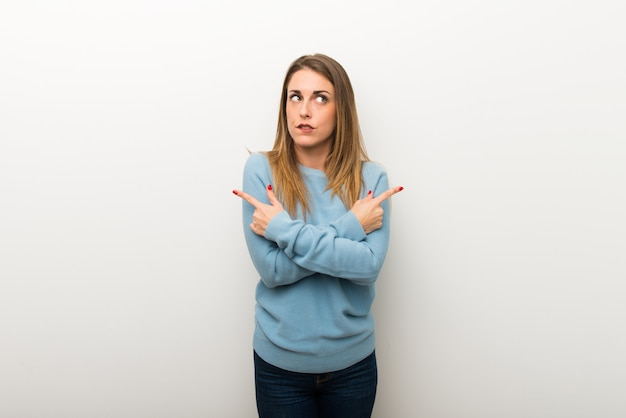 Blonde woman on isolated white background pointing to the laterals having doubts