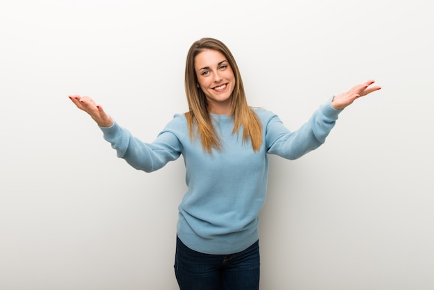 Blonde woman on isolated white background presenting and inviting to come with hand