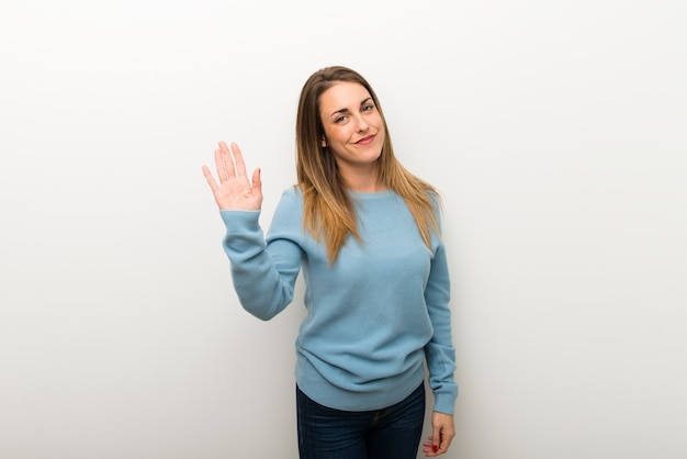 Blonde woman on isolated white background saluting with hand with happy expression