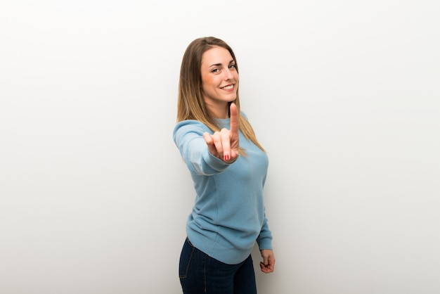 Blonde woman on isolated white background showing and lifting a finger