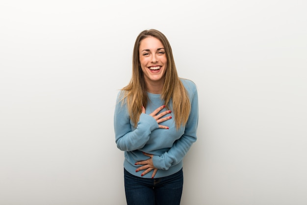 Blonde woman on isolated white background smiling a lot while putting hands on chest
