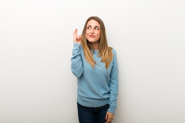 Blonde woman on isolated white background with fingers crossing and wishing the best