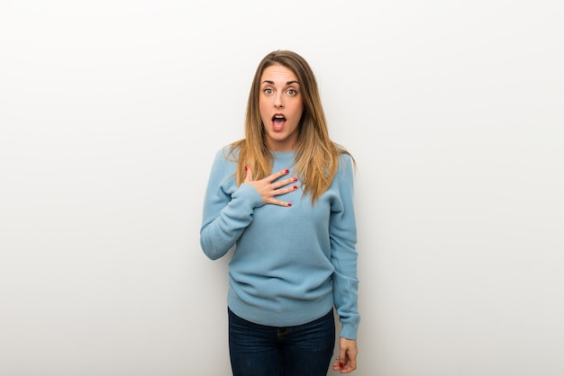 Blonde woman on isolated white wall surprised and shocked while looking right