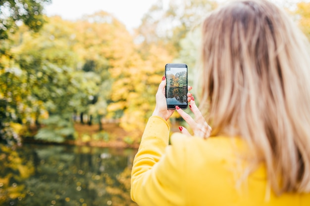 Blonde woman it yellow coat makes photo on cell phone in the park in autumn.close up, selective focus.