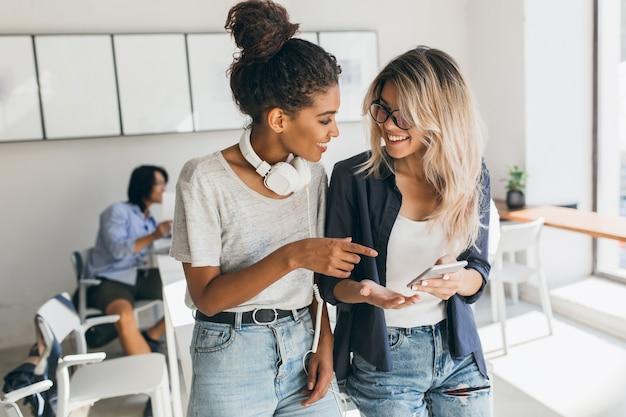 Donna bionda in jeans e occhiali che tiene smartphone mentre parla con un amico africano in ufficio. studentessa abbastanza internazionale in cuffie che trascorre del tempo con i compagni universitari.