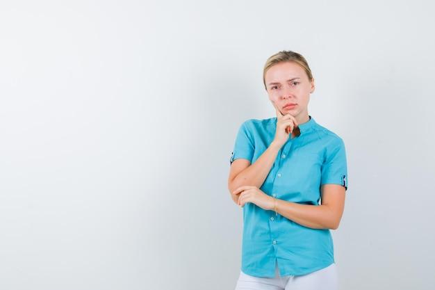 파란색 블라우스에 턱에 손을 유지하고 잠겨있는 고립 된 찾고 금발의 여자