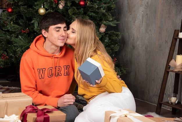ブロンドの女性が家のインテリアでクリスマスプレゼントで彼女のボーイフレンドにキスします。