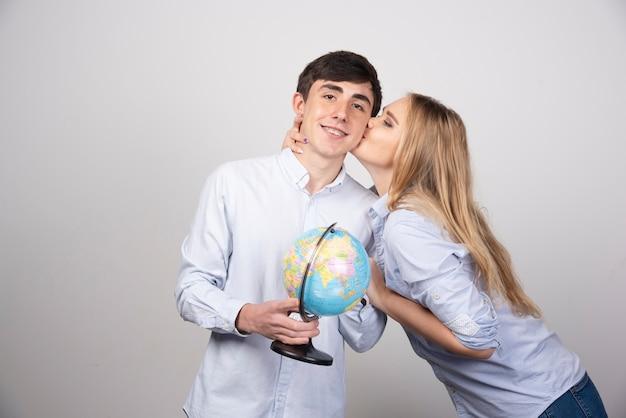 Блондинка женщина целует в щеку модель брюнетка парень с земным шаром