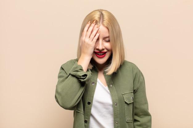 Светловолосая женщина смеется и хлопает по лбу, как будто говоря: «о! я забыл или это была глупая ошибка