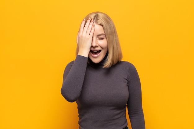 Блондинка смеется и хлопает по лбу, как будто говоря о! я забыл или это была глупая ошибка
