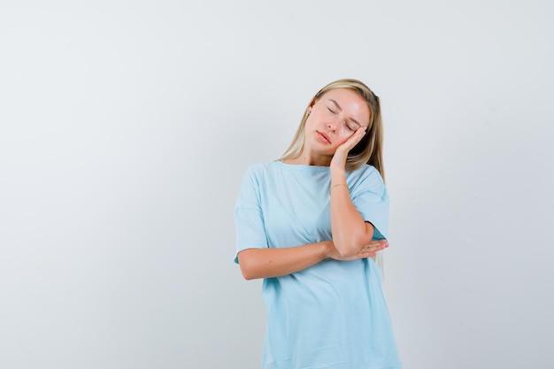 금발의 여자는 손바닥에 뺨을 기대고 파란색 티셔츠에 눈을 감고 졸린 표정을지었습니다.