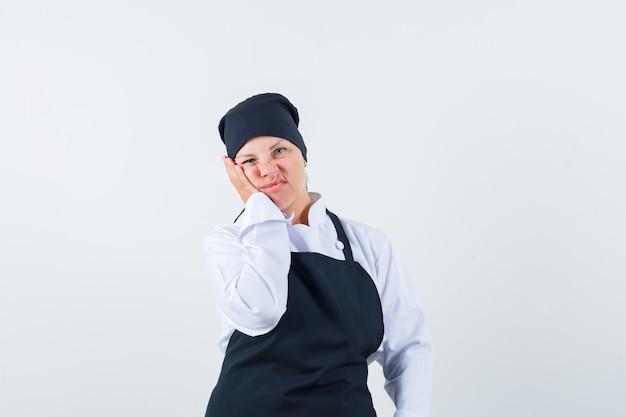 Donna bionda che si appoggia la guancia sul palmo, che fa smorfie in uniforme nera del cuoco e sembra scontento, vista frontale Foto Gratuite