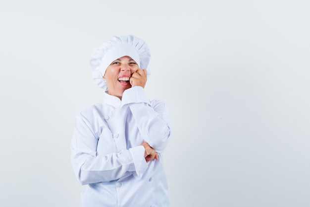 Donna bionda che si appoggia la guancia sul palmo, sorridente in uniforme bianca del cuoco e che sembra carina.