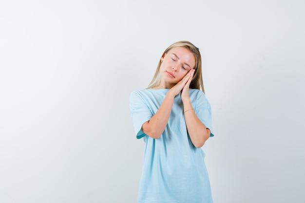 Donna bionda che si appoggia la guancia sui palmi come cuscino in maglietta blu e sembra assonnata