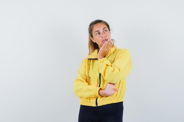 Donna bionda che si appoggia il mento sul palmo mentre pensa a qualcosa in bomber giallo e pantaloni neri e sembra pensieroso