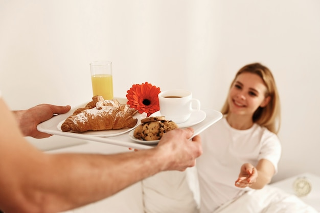 Blonde woman lies in the bed and looks at tray with breakfast and takes it