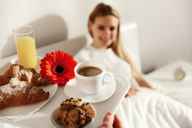 Blonde woman lies in the bed and looks at tray with breakfast