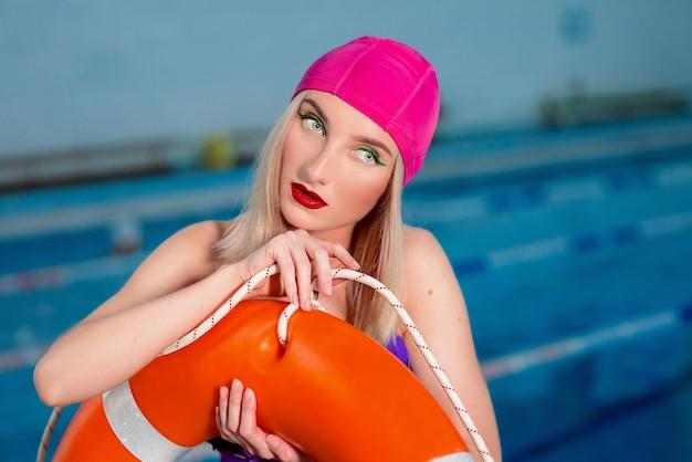 ライフブイと一緒にスイミングプールでスイムキャップと水着でメイクアップと金髪の女性のライフガード