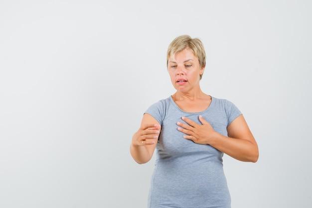 Donna bionda in maglietta azzurra che finge di leggere notizie sul telefono e sembra sorpresa, vista frontale.