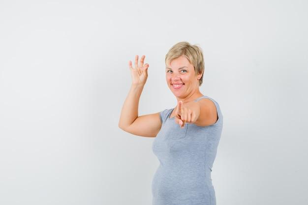 Donna bionda in maglietta azzurra che mostra segno giusto e che indica e che sembra gioiosa, vista frontale.