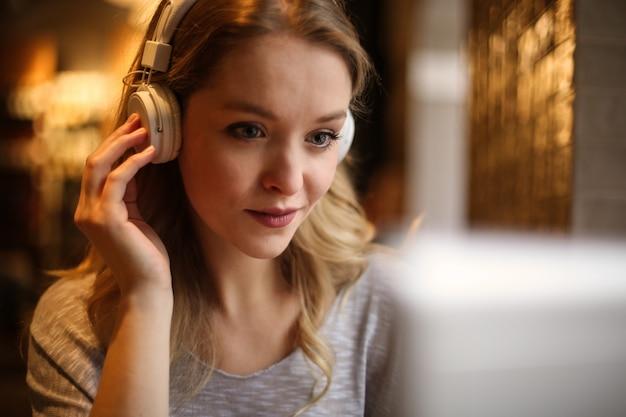 Blonde woman listening to music on headphones