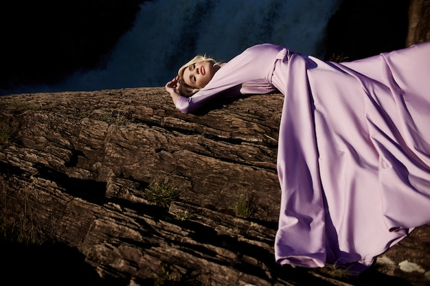 Blonde woman in a long pink dress lying on a stone