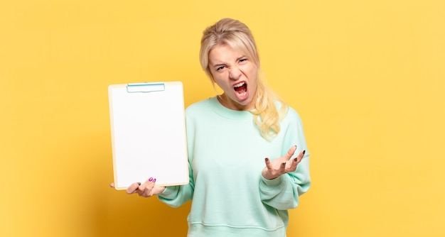 Блондинка выглядит сердитой, раздраженной и разочарованной, кричит, черт возьми, или что с тобой не так