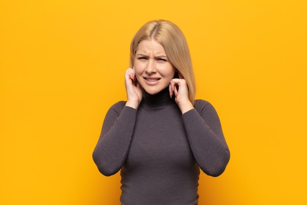 Blonde woman looking angry, stressed and annoyed, covering both ears to a deafening noise, sound or loud music