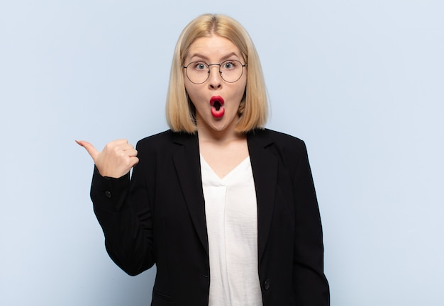 Blonde woman looking astonished in disbelief, pointing at object on the side and saying wow, unbelievable