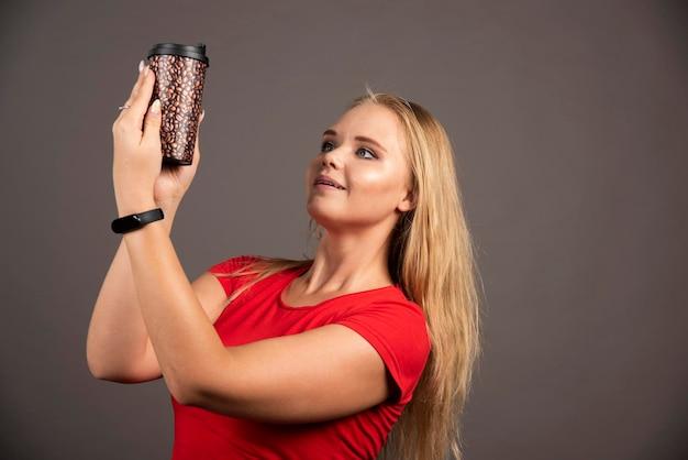 Блондинка женщина, глядя на чашку кофе на темном фоне. фото высокого качества