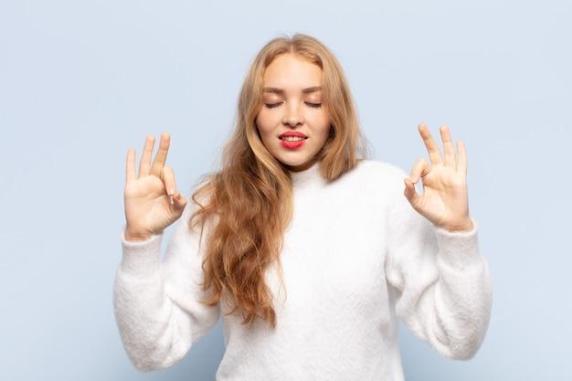 集中して瞑想しているように見え、満足してリラックスしていると感じ、考えたり選択したりする金髪の女性