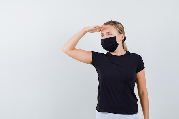 黒のtシャツ、白いズボンで頭上に手を渡して遠くを見ているブロンドの女性