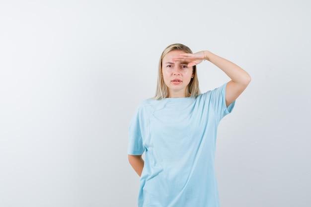 青いtシャツを着て頭上に手を渡して遠くを見て、集中して見えるブロンドの女性