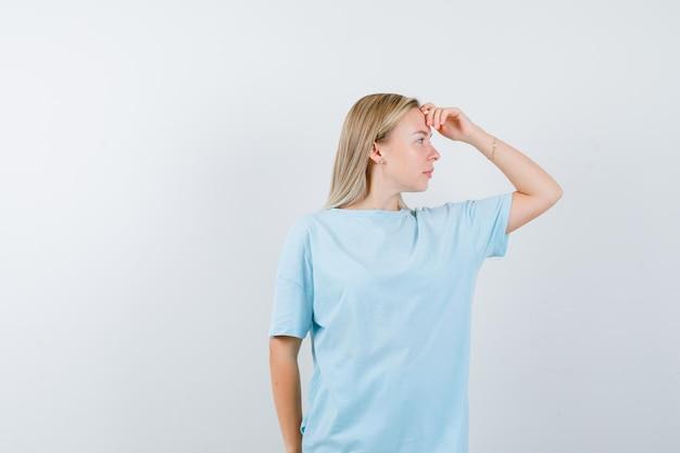 파란색 티셔츠에 머리 위에 손으로 멀리보고 초점을 맞춘 금발의 여자