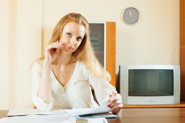 Blonde woman looking financial documents at table